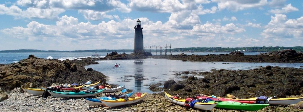kayaks on a ledge by lighthouse