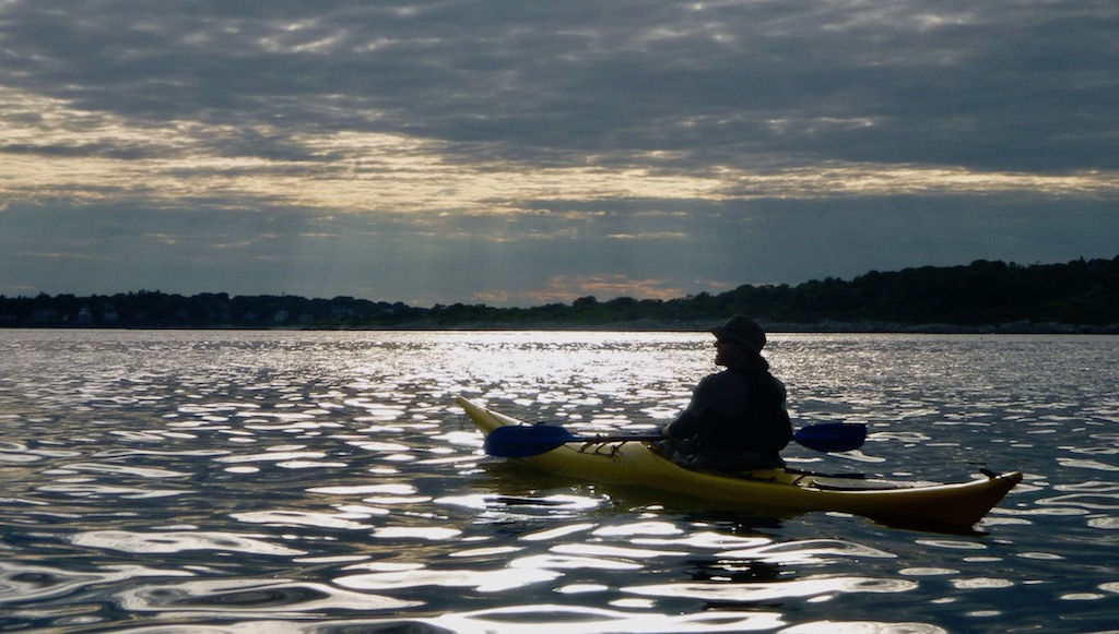 kayaker silhouetted on reflecting sea