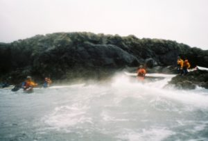 Kayakers landing in surf on rocks