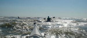sea kayakers paddling in rough water