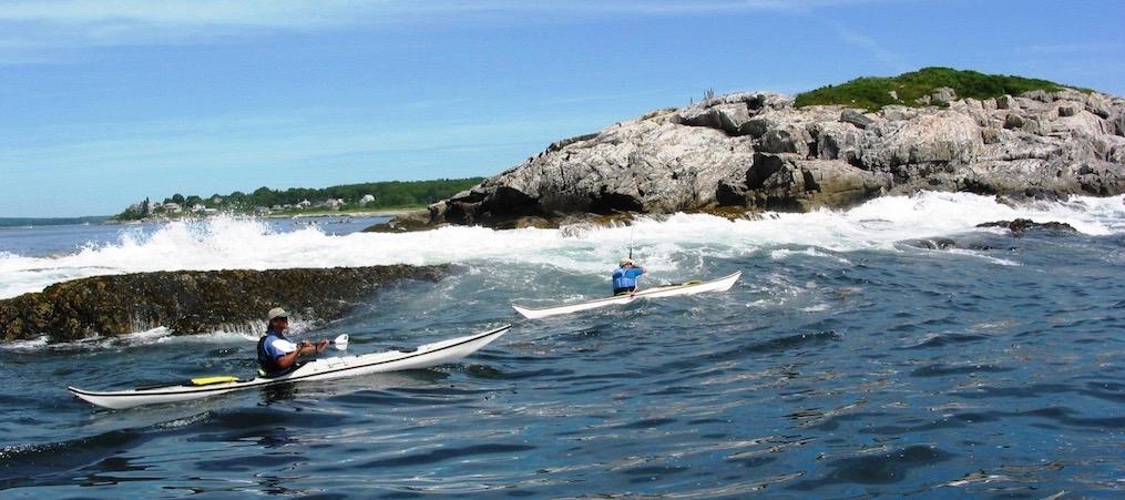 kayakers paddling near rocks