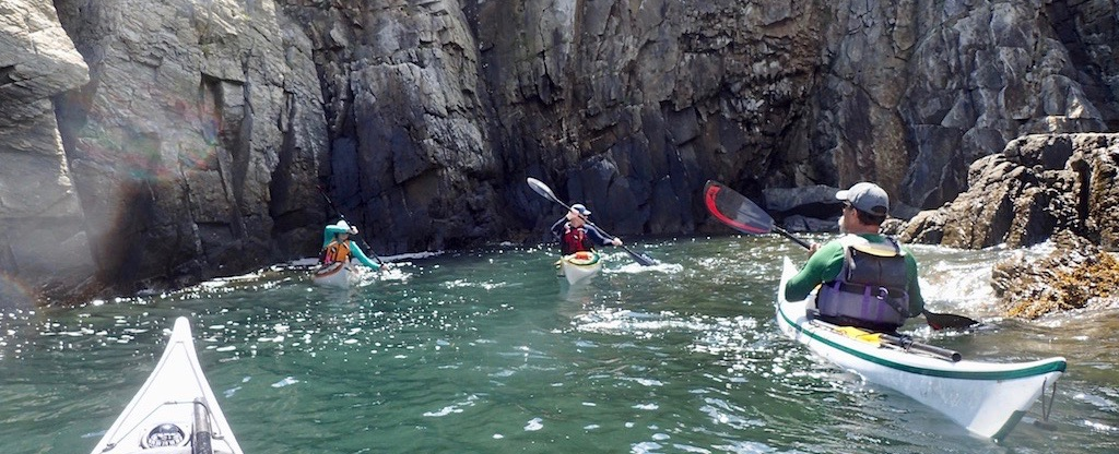 kayakers maneuvering sideways by rocky cliffs