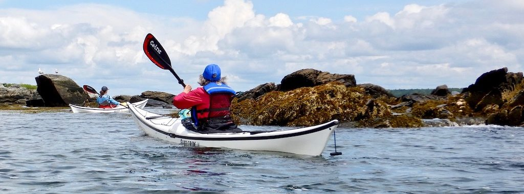 sea kayaking by the rocky shore of Peaks Island, Maine